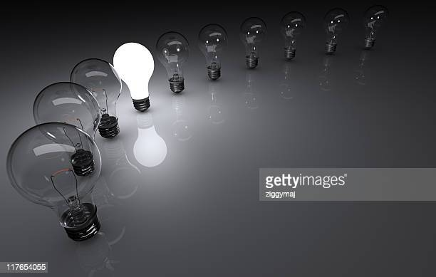 Line of 11 dull light bulbs with one illuminated in middle
