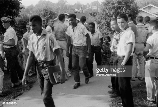 A line of African American boys walk through a crowd of white boys on their way to school Clinton Tennessee December 4 1956