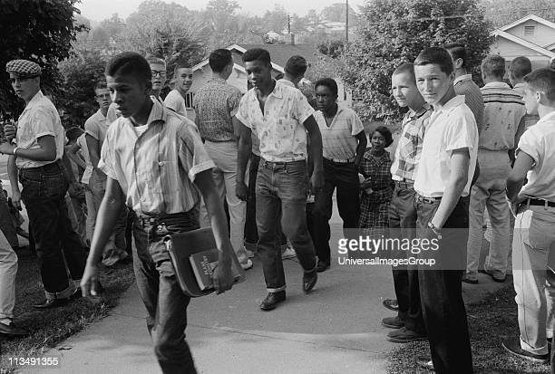 Line of African American boys walking through a crowd of white boys during a period of violence related to school integration Little Rock Arkansas 4...