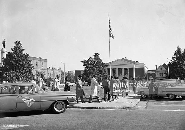 A line of African American student protestors march before an Orangeburg church flying the flags of the country the state and the Confederacy...