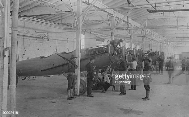 Line of airplanes is being assembled under the watchful eye of a gun-toting soldier as they are being completed to be sent to the European war; the...