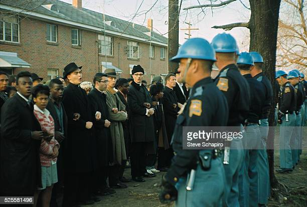 A line of Alabama State Police face down a line of civil rights activists who stand with arms linked in unity The protestors are about to begin the...