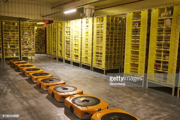 A line of automated transport robots sit before operating to move shelving units containing goods at Amazoncom Inc's new fulfillment center in...