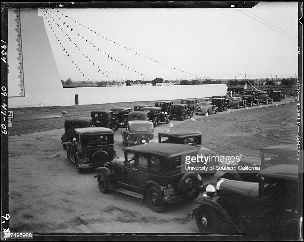 Line of automobiles at opening day of Drivein movie theatre