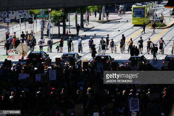 """Line of bicycles and cars escorts protesters during a """"Defund the Police"""" march from King County Youth Jail to City Hall in Seattle, Washington on..."""