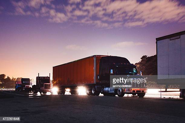 A line of big rig trucks during sun rise