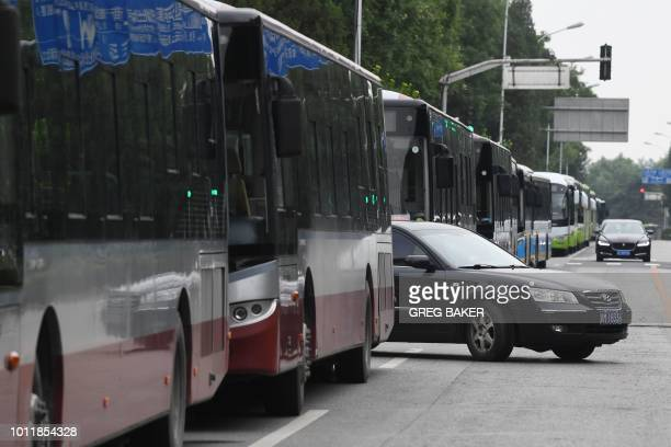 A line of buses is seen along a street near China's Banking Regulatory Commission in Beijing on August 6 2018 Hundreds of police swarmed the streets...