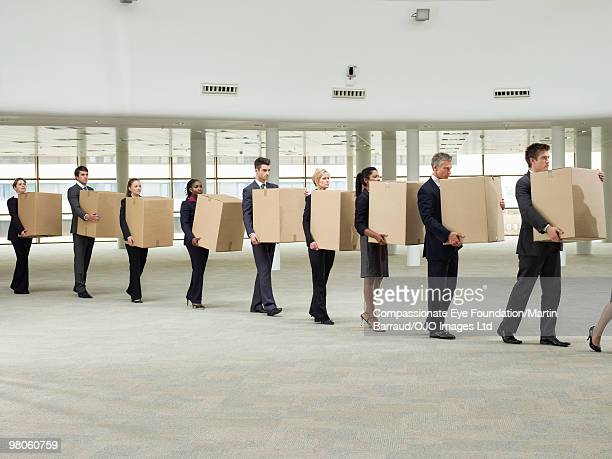 line of business people carrying cardboard boxes - downsizing unemployment stock pictures, royalty-free photos & images