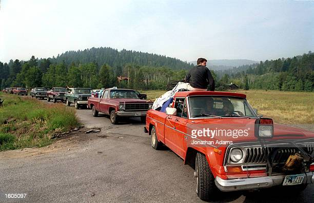 A line of cars evacuate the Indian Paintbrush subdivision July 26 2001 in Wilson WY after a forest fire began moving in the direction of their homes