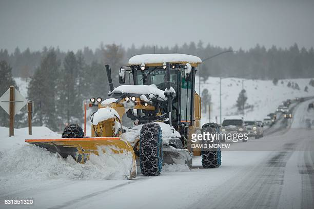 A line of cars follows a tractor plowing snow near Mammoth Lakes California January 9 2017 as a series of strong storms moves through the western US...