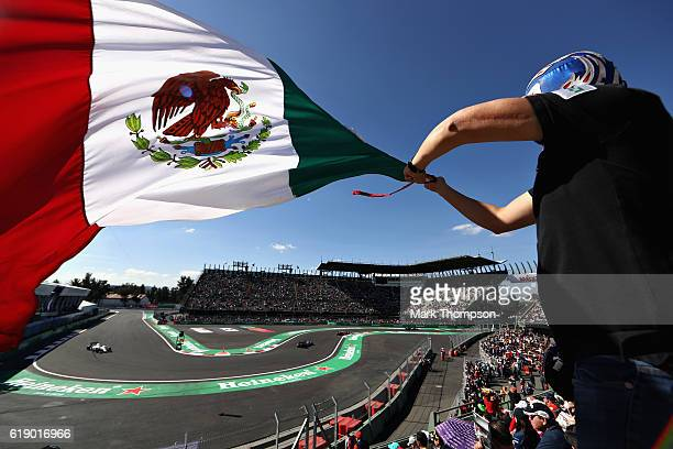 Line of cars pass as a fan waves a Mexican flag during final practice for the Formula One Grand Prix of Mexico at Autodromo Hermanos Rodriguez on...