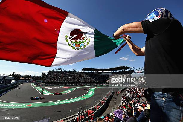A line of cars pass as a fan waves a Mexican flag during final practice for the Formula One Grand Prix of Mexico at Autodromo Hermanos Rodriguez on...