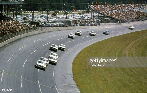A line of cars race around a turn during the Daytona 500 race at Daytona Speedway circa 1964