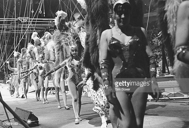 A line of circus showgirls dressed a sequinned leotards elbow gloves and feathered headgear and clowns in polkabot costumes wave as they leave the...