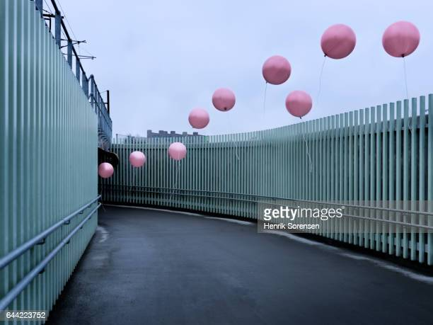 A line of colored balloons flying out of tunnel