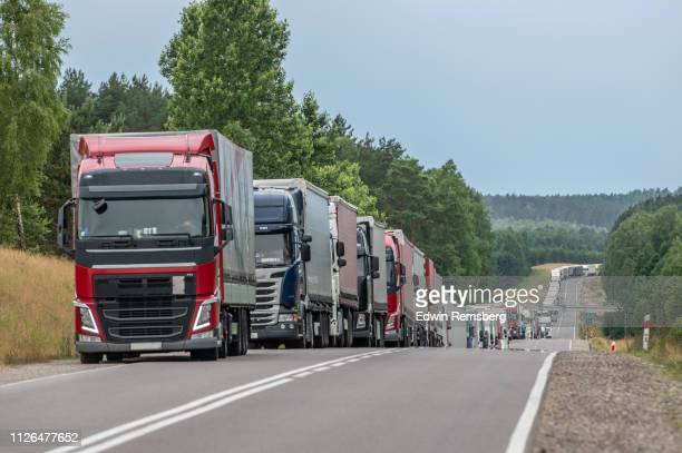 line of commercial trucks waiting to cross border - poland stock pictures, royalty-free photos & images
