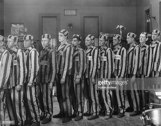 A line of convicts stands in a prison library wearing numbered identification patches striped uniforms and caps in a still from director Raoul...