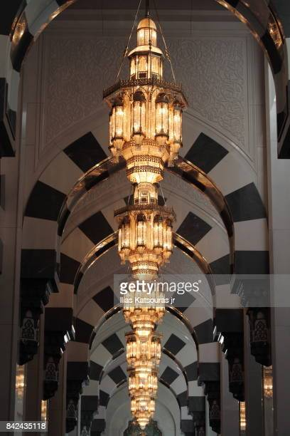 A line of crystal chandeliers under graceful arches at the south riwaq of the main prayer hall of the Sultan Qaboos Grand Mosque in Muscat, Oman