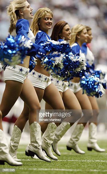 A line of Dallas Cowboy cheerleaders lock arms and cheer for the hometeam during a game against the Arizona Cardinals at Texas Stadium on October 5...