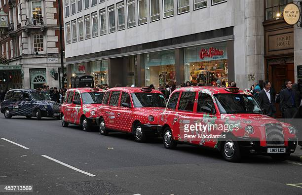 A line of decorated London taxis is seen outside the largest Cath Kidston store in the world at 180 Piccadilly on December 5 2013 in London England...