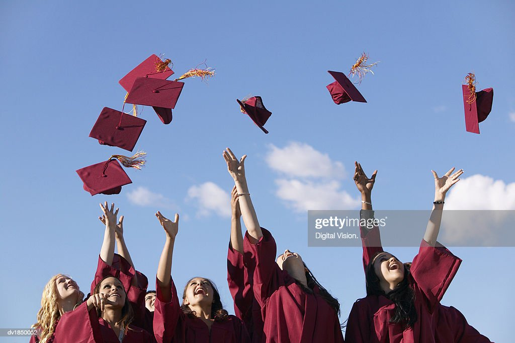 Line of Female Students Throwing Their Mortar Boards in the Air at Graduation : Stock Photo