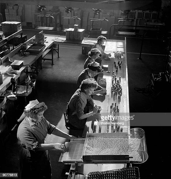 Line Of Female Workers Fill Bottles On A Tablet Belt At The SPEKE Company In Garston