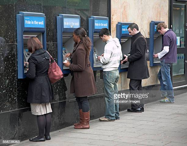 Line of five people at cash point machines London England