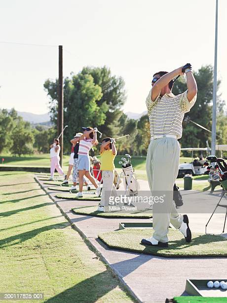 line of golfers mid swing on driving range - driving range stock pictures, royalty-free photos & images