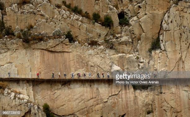 line of hikers along the caminito del rey walkway hanging from the cliffs of el chorro gorge above guadalhorce river - caminito del rey fotografías e imágenes de stock