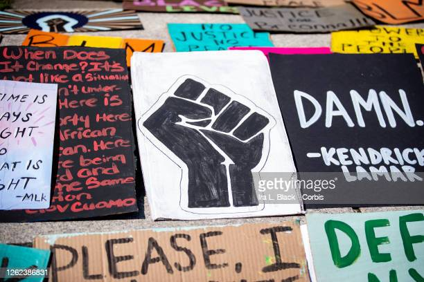 A line of homemade protest signs including a black power fist lay on the steps for people to pick up and use for the march in Cadman Plaza Brooklyn...