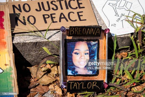 A line of homemade protest signs lay on the steps including one with a picture of Breonna Taylor for people to pick up and use for the march in...