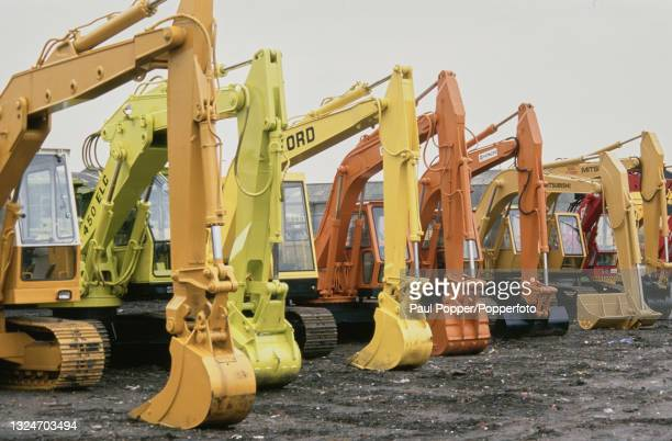 Line of imported tracked diggers and excavators, intended for heavy construction work, await auction at a yard in Liverpool, England in April 1988....