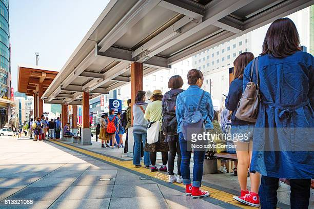 Line of Japanese people waiting for bus at Nagano station