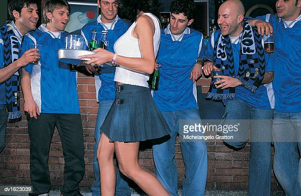 line of laddish football fans in a bar watching a barmaid carrying a tray of drinks - ongewenste intimiteit stockfoto's en -beelden