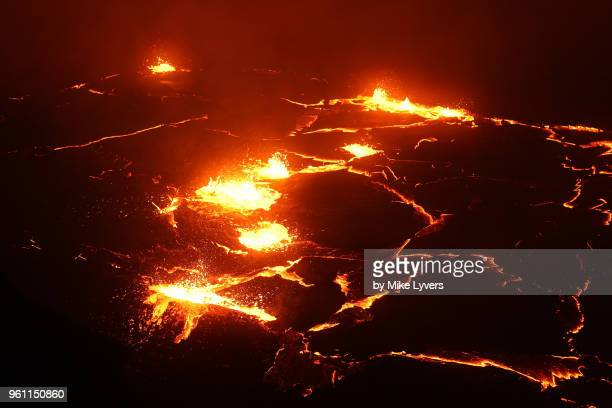 a line of lava fountains extends across the lava lake, pu'u o'o crater, may 2011. - pu'u o'o vent stock pictures, royalty-free photos & images