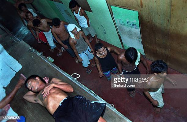 Line of men clean the floor by scrapping coconut shells across the floor surface with their feet. This is the cell block for Batang City Jail gang,...