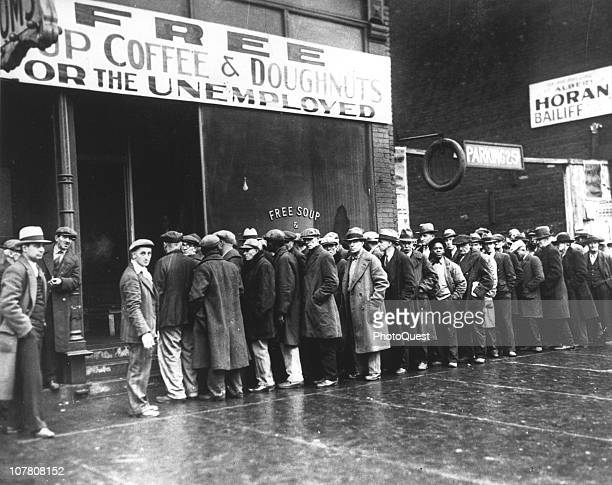 A line of men wait outside a soup kitchen opened durin the depression by mobster Al Capone Chicago Illinois February 1931 The storefront sign reads...