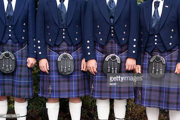 line of men wearing purple kilts - kilt stock photos and pictures