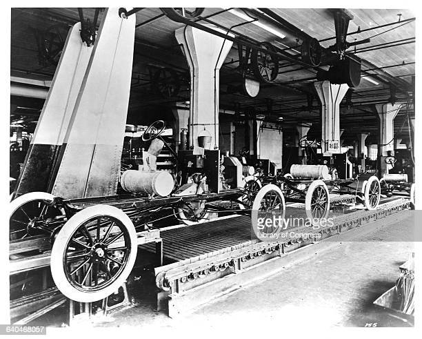 A line of Model T automobiles await further assembly The Highland Park Ford Plant in Michigan is considered to be the birthplace of moving assembly...