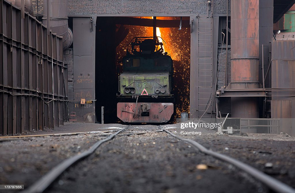 A line of molten metal pours into a cauldron on a train wagon in the converter shop at OAO Mechel's metallurgical plant in Chelyabinsk, Russia, on Wednesday, July 17, 2013. Mechel, the country's largest producer of coking coal for steelmakers has begun operating its $700m rail production line which can produce 100 meter rails. Photographer: Andrey Rudakov/Bloomberg via Getty Images
