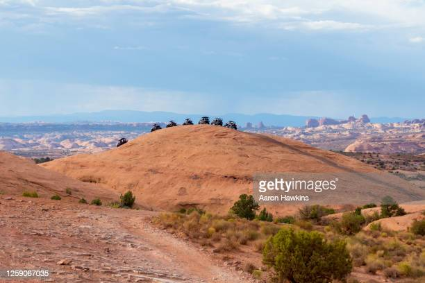 line of off road side by side vehicles on sandstone summit in hell's revenge area near moab utah - sandy utah stock pictures, royalty-free photos & images