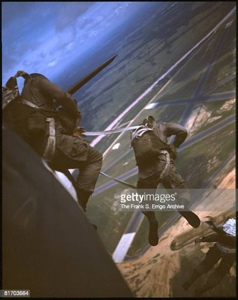 Line of paratroopers jump out of a plane during training exercises above Fort Benning, Georgia, 1943.