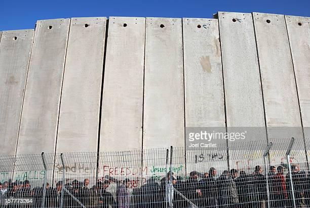Línea de personas en pared en Palestina de altura
