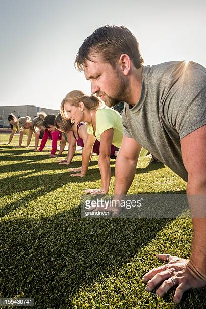 Line of people doing pushups or planks outside on grass
