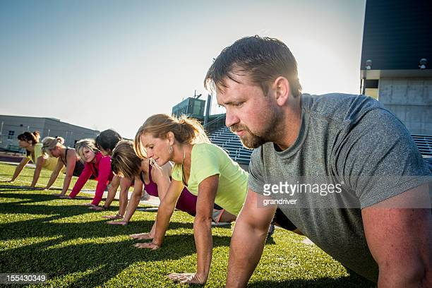 Line of people doing pushups outside on grass