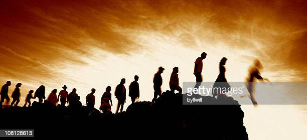 line of people walking single file off cliff - suicide stock photos and pictures