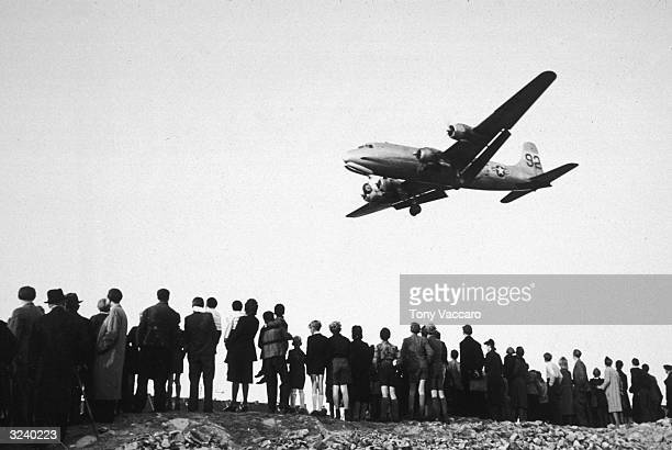 A line of people watch as a supply plane arrives to deliver food and other staples during the Berlin Airlift after World War II West Germany