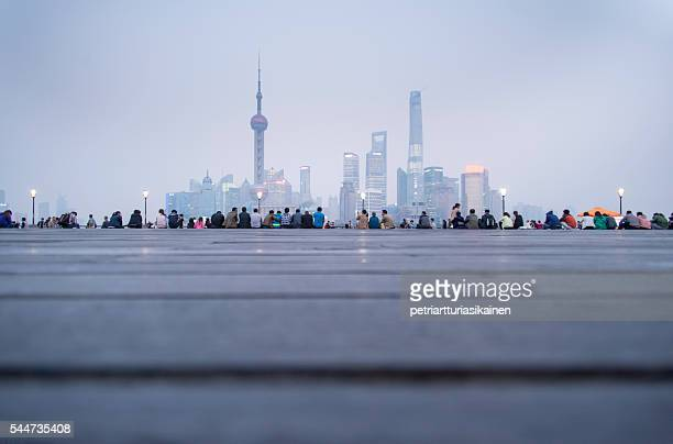 Line of people with Shanghai skyline at dusk.
