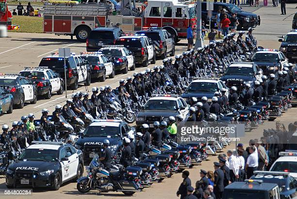 A line of police motorcycle officers line the entrance to the stadium as the procassion enters for the memorial service for Euless police officer...