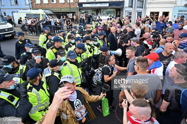 Line of police officers face a group of anti-immigration protesters on a main road in Dover on the south-east coast of England, on September 5 as...